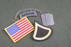 US ARMY Private First Class rank patch, ranger tab, flag patch and dog tag on olive green unifor Stock Images