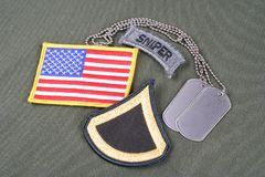 US ARMY Private First Class rank patch, sniper tab, flag patch and dog tag on olive green unifor. M background Stock Photos