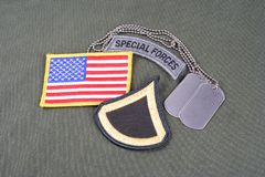 US ARMY Private First Class rank patch, special forces tab, flag patch and dog tag on olive gree Stock Images
