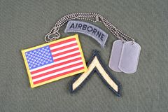 US ARMY Private rank patch, airborne tab, flag patch and dog tag on olive green uniform. Background Royalty Free Stock Images