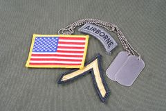 US ARMY Private rank patch, airborne tab, flag patch and dog tag on olive green uniform. Background Stock Images