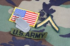 US ARMY Private rank patch, branch tape, flag patch and dog tags on woodland camouflage uniform. Background Royalty Free Stock Photo