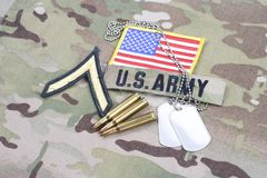 US ARMY Private rank patch, flag patch, with dog tag with 5.56 mm rounds on camouflage uniform. Background Stock Image