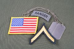 US ARMY Private rank patch, ranger tab, flag patch and dog tag on olive green uniform Stock Image