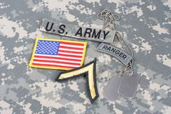US ARMY Private rank patch, ranger tab, flag patch,  with dog tag on camouflage uniform Royalty Free Stock Images
