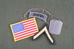 US ARMY Private rank patch, sniper tab, flag patch and dog tag on olive green uniform. Background Stock Image