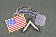 US ARMY Private rank patch, special forces tab, flag patch and dog tag on olive green uniform. Background Royalty Free Stock Photography