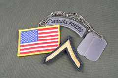 US ARMY Private rank patch, special forces tab, flag patch and dog tag on olive green uniform. Background Stock Photography