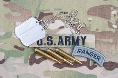 US ARMY ranger tab, flag patch, with dog tag and 5.56 mm rounds on camouflage uniform Royalty Free Stock Image