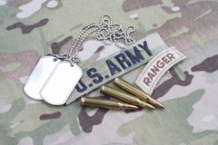 US ARMY ranger tab, flag patch, with dog tag and 5.56 mm rounds on uniform. US ARMY ranger tab, flag patch, with dog tag and 5.56 mm rounds on camouflage uniform Royalty Free Stock Image