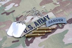 US ARMY ranger tab, flag patch, with dog tag and 5.56 mm rounds. On camouflage uniform Royalty Free Stock Photography