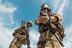 US Army Rangers with weapons. US Army Rangers pointing weapons to the camera detaining person. Low angle view Stock Photos