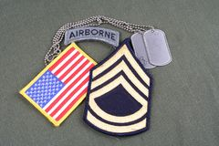 US ARMY Sergeant First Class rank patch, airborne tab, flag patch and dog tag on olive green uni. Form background Stock Image