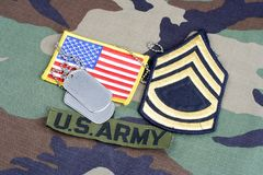 US ARMY Sergeant First Class rank patch, branch tape, flag patch and dog tags on woodland camouflag. E uniform Royalty Free Stock Photos