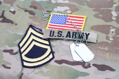 US ARMY Sergeant First Class rank patch, flag patch, with dog tag on camouflage uniform. Background Stock Photo