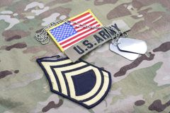 US ARMY Sergeant First Class rank patch, flag patch, with dog tag on camouflage uniform. Background Stock Photos