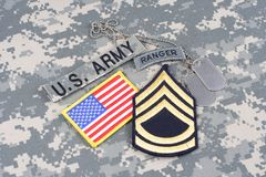 US ARMY Sergeant First Class rank patch, ranger tab, flag patch,  with dog tag on camouflage unif Stock Images