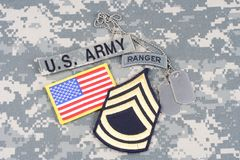 US ARMY Sergeant First Class rank patch, ranger tab, flag patch,  with dog tag on camouflage unif Stock Image