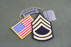 US ARMY Sergeant First Class rank patch, ranger tab, flag patch and dog tag on olive green unifo Royalty Free Stock Images