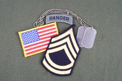 US ARMY Sergeant First Class rank patch, ranger tab, flag patch and dog tag on olive green unifo Stock Photo