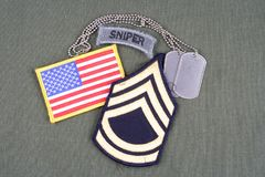 US ARMY Sergeant First Class rank patch, sniper tab, flag patch and dog tag on olive green unifo. Rm background Stock Images