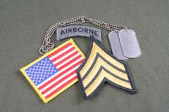 US ARMY Sergeant rank patch, airborne tab, flag patch and dog tag on olive green uniform. Background Royalty Free Stock Images