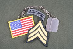 US ARMY Sergeant rank patch, airborne tab, flag patch and dog tag on olive green uniform. Background Royalty Free Stock Photos