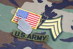 US ARMY Sergeant rank patch, branch tape, flag patch and dog tags on woodland camouflage uniform. Background Royalty Free Stock Images