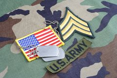 US ARMY Sergeant rank patch, branch tape, flag patch and dog tags on woodland camouflage uniform. Background Stock Photo
