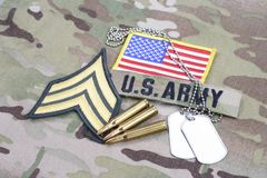 US ARMY Sergeant rank patch, flag patch, with dog tag with 5.56 mm rounds on camouflage uniform. Background royalty free stock images