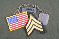 US ARMY Sergeant rank patch, ranger tab, flag patch and dog tag on olive green uniform Royalty Free Stock Images