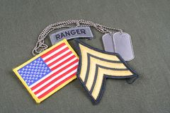 US ARMY Sergeant rank patch, ranger tab, flag patch and dog tag on olive green uniform Stock Photography