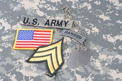 US ARMY Sergeant rank patch, ranger tab, flag patch,  with dog tag on camouflage uniform Royalty Free Stock Photo