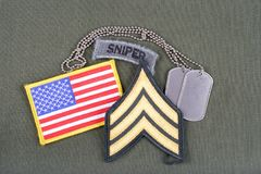 US ARMY Sergeant rank patch, sniper tab, flag patch and dog tag on olive green uniform. Background Stock Photo