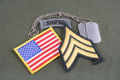 US ARMY Sergeant rank patch, sniper tab, flag patch and dog tag on olive green uniform. Background Royalty Free Stock Photo