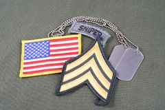 US ARMY Sergeant rank patch, sniper tab, flag patch and dog tag on olive green uniform. Background Stock Photos