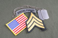 US ARMY Sergeant rank patch, special forces tab, flag patch and dog tag on olive green uniform. Background Royalty Free Stock Photography