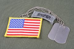 US ARMY sniper tab with dog tag and flag patch on olive green uniform. Background Royalty Free Stock Images