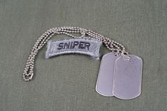US ARMY sniper tab with dog tag and flag patch on olive green uniform. Background Stock Images