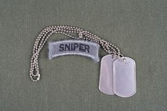 US ARMY sniper tab with dog tag  and flag patch on olive green uniform. Background Royalty Free Stock Photos