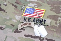 US ARMY sniper tab, flag patch, with dog tag on camouflage uniform. Background Stock Photos