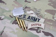 US ARMY sniper tab, flag patch, with dog tag and 5.56 mm rounds and 5.56 mm rounds on uniform. US ARMY sniper tab, flag patch, with dog tag and 5.56 mm rounds Royalty Free Stock Photos