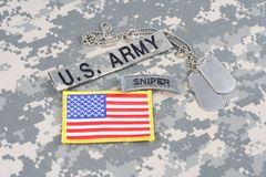 US ARMY sniper tab, flag patch,  with dog tags on camouflage uniform. Background Stock Photos