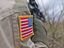 US Army soldier in action. Flag patch closeup and rifle on the background Stock Photos