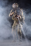 US Army Soldier in Action in the Fog. Portrait of US Army Soldier in Action with Four-eyed night vision goggles in the Smoke; Dark and Foggy Background; Beam of Stock Image