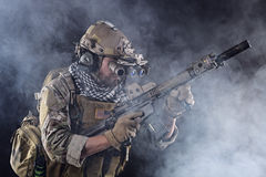 US Army Soldier in Action with goggles in the Smoke. Portrait of US Army Soldier in Action with Four-eyed night vision goggles in the Smoke; Dark and Foggy stock image