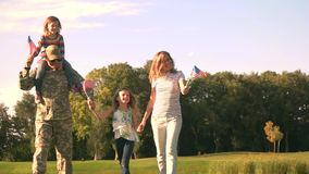 US army soldier with family in park. Handsome soldier reunited with family on a sunny day stock footage