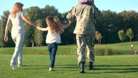 US army soldier with his wife holding daughter hands. Father with daughter on shoulders walking, back view stock footage
