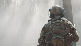 US Army soldier run through the smoggy forest during battle