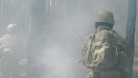US Army soldiers run through the smoggy forest during battle